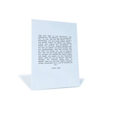 """Weiße Postkarte mit Zitat von Steve Jobs """"Das hier geht an die Verrückten, die Außenseite, die Rebellen, die Unruhestifter, ..."""""""