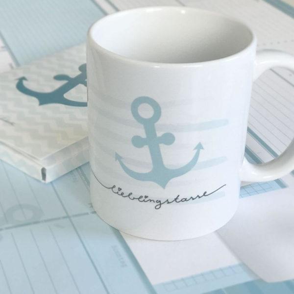 """weiße Keramiktasse mit blauem Ankerdesign, blauen Streifen und dem Schriftzug """"Lieblingstasse"""""""