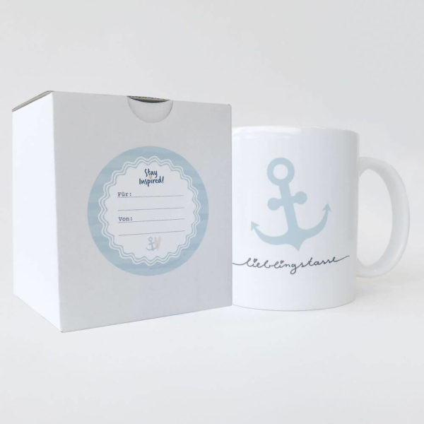 """weiße Keramiktasse mit blauen Streifen und maritimen Anker sowie dem Aufdruck """"Lieblingstasse"""", verpackt in passender Schachtel mit blauem Geschenkaufkleber"""