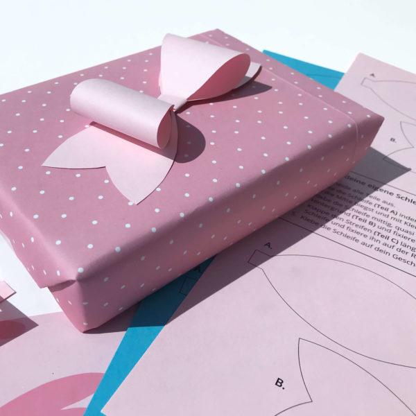 rosa gepunktete Geschenkschachtel mit rosafarbener Papierschleife