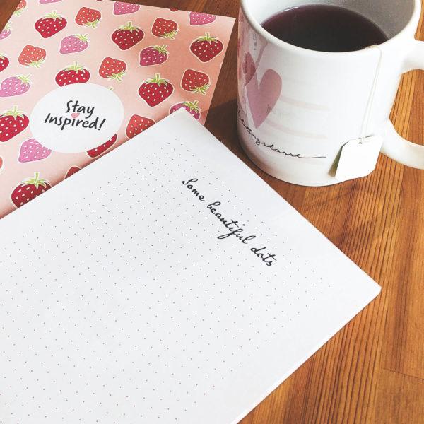 Notizblock mit Punkteraster und Erdbeermotiv sowie Teetasse mit Herzmotiv